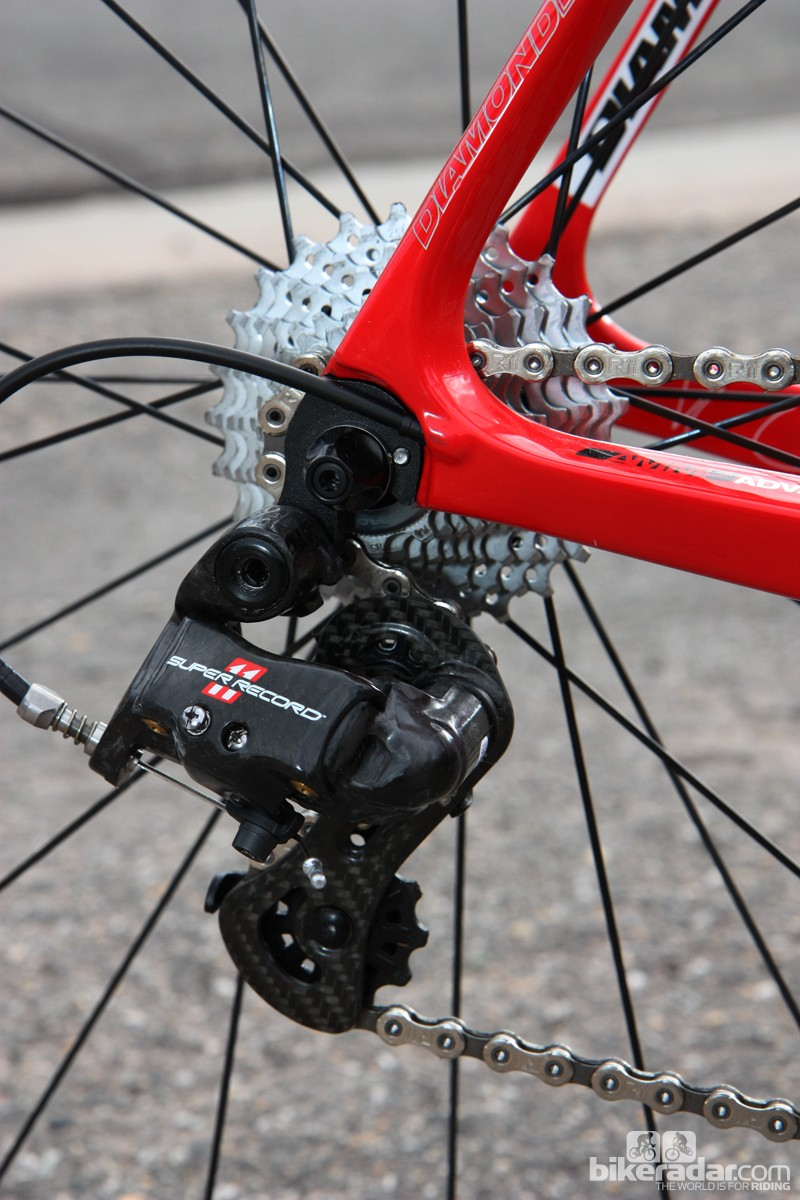 The Campagnolo Super Record rear derailleur is mounted to a replaceable aluminum hanger. The cable is fed through the chain stay