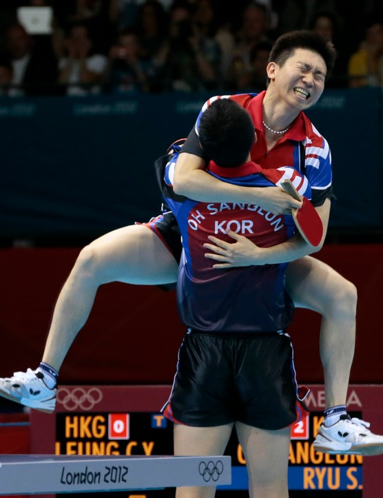 South Korea's Oh Sang-eun and Ryu Seung-min, top, celebrate beating Hong Kong's Jiang Tianyi and Leung Chu Yan in a team table tennis semifinal