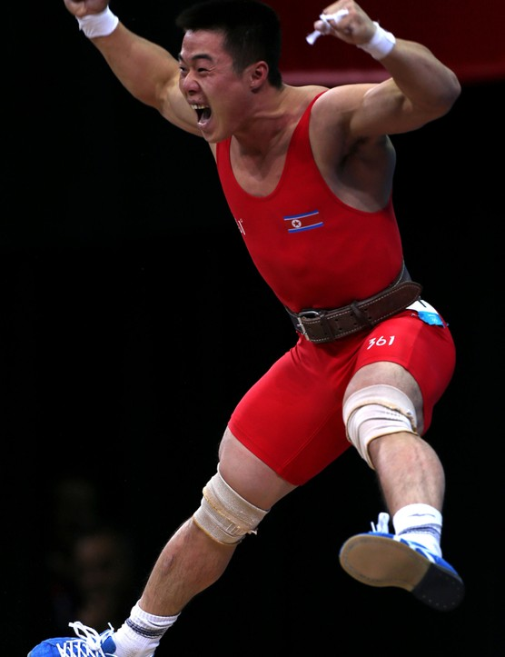 North Korea's Un Guk Kim celebrates lifting a world record in the Olympic clean and jerk