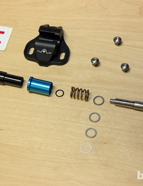 The Ultralite pedals have less than a dozen pieces per pedal (some of the pressed-in bits such as bushings and bearings are hidden inside the black aluminum cylinder at left). The washers at far right can be used to slightly adjust the pedal stance width while the preload for the retention system can be adjusted by adding extra washers behind the spring