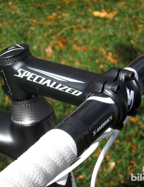 A Specialized S-Works classic-bend carbon fiber handlebar is clamped in a forged aluminum stem