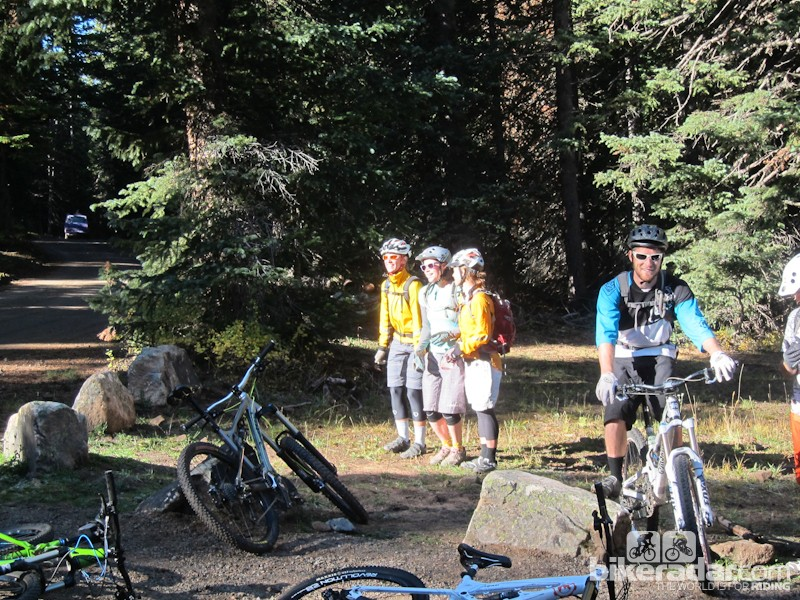 Fresh off the shuttle, riders huddle in a sliver of sunlight to try to warm up in the near-freezing temps found on Geyser Pass