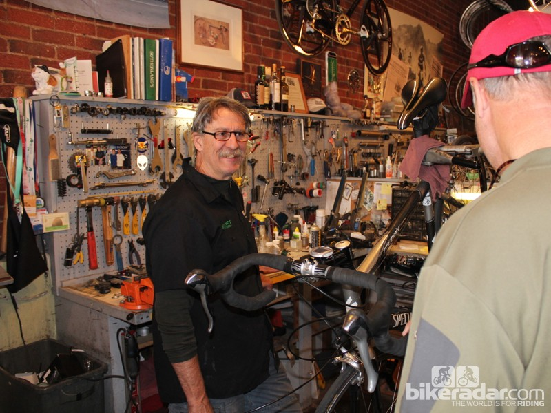 Owner Peter Chisolm talking with a customer from his usual spot behind a workstand