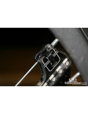 The LED unit fixes to spokes by cable ties, with vibration-absorbing rubber strips between the two