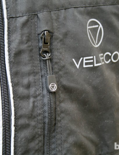 A zipped pocket and reflective piping on the Veleco Re:Cycle Softshell Cycling Jacket