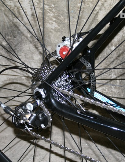 Box-section chainstays taper and curve into the slender seatstays. The non-driveside features the calliper mount and bracing strut between the two stays