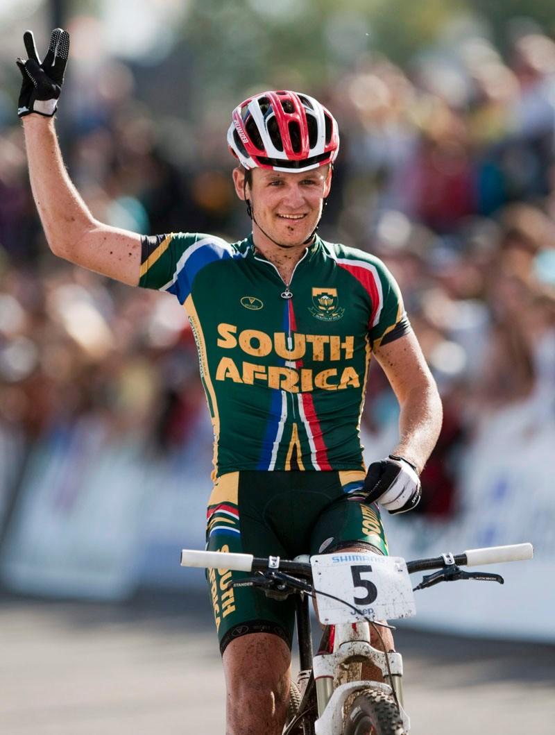 Burry Stander of South Africa flashes a three as he crosses the finish in third place in the men's Elite cross-country on Saturday Sept. 4, 2010, at the Mountain Bike and Trials World Championships at Mont-Sainte-Anne, Canada