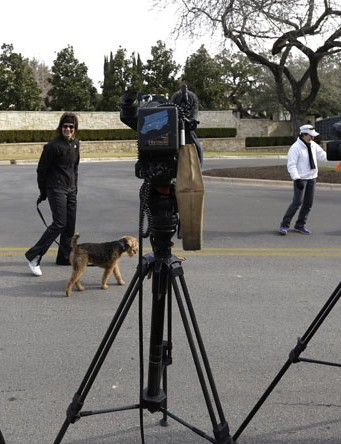 Neighbors walk past the home of cyclist Lance Armstrong and waiting media, Monday, Jan. 14, 2013, in Austin, Texas