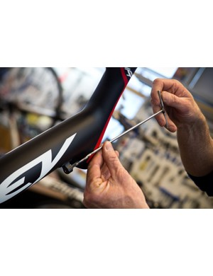 Competitive Cyclist mechanics are detail-oriented. Here, a cable housing stop is tapped