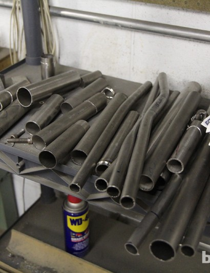 Experimental titanium tubes sit on a shelf in the workshop