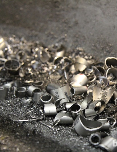 Bits of titanium scraps sit in the catch basin of one of the lathes at Dean Titanium Bicycles