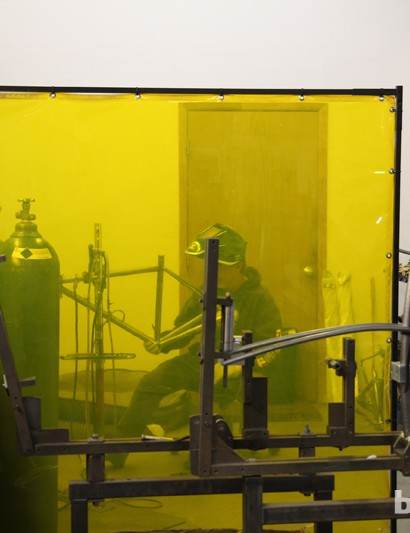A yellow screen protects other workers from the intense flash of the welding torch