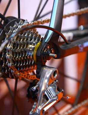 The thick machined aluminum rear derailleur hanger is bolted to a carbon fiber dropout