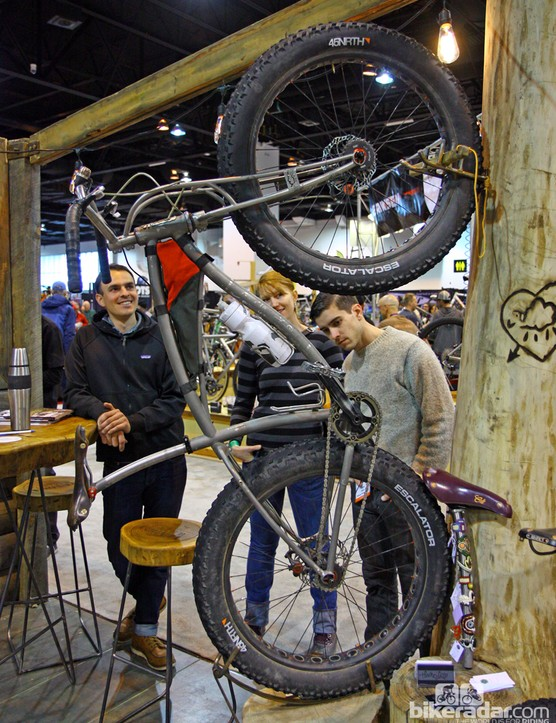 A trio of NAHBS attendees stand in admiration of this Black Sheep snow bike