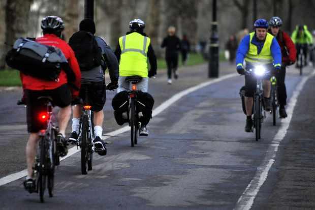Commuters make their way through Hyde Park, London, UK