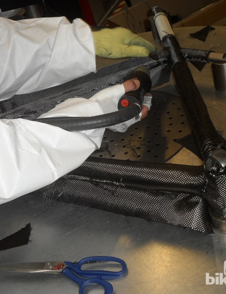 Once all the wax forms have the carbon weaves stretched over them, they're attached together and the carbon is stitched and tied. Then, a very thin finishing layer of pre-preg is heated on. This has no structural importance, it's used to make the finished frame look cleaner. We'd like to see a raw frame made available