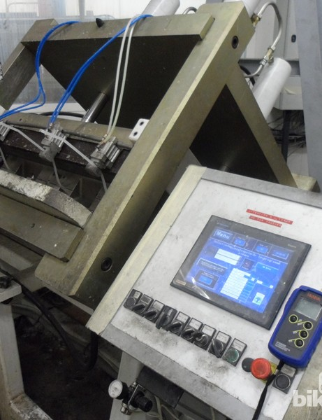 The mould is loaded into this computer-controlled cage, where the resin is injected and three vacumn pumps draw out the air and pull the resin through the structure