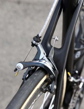 A stainless steel number plate holder is sandwiched between the Shimano Dura-Ace BR-9000 brake caliper and brake bridge