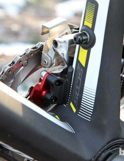 The front derailleur is mounted to a stout aluminum block at the base of the seat tube. The red anodized bit is a built-in chain catcher