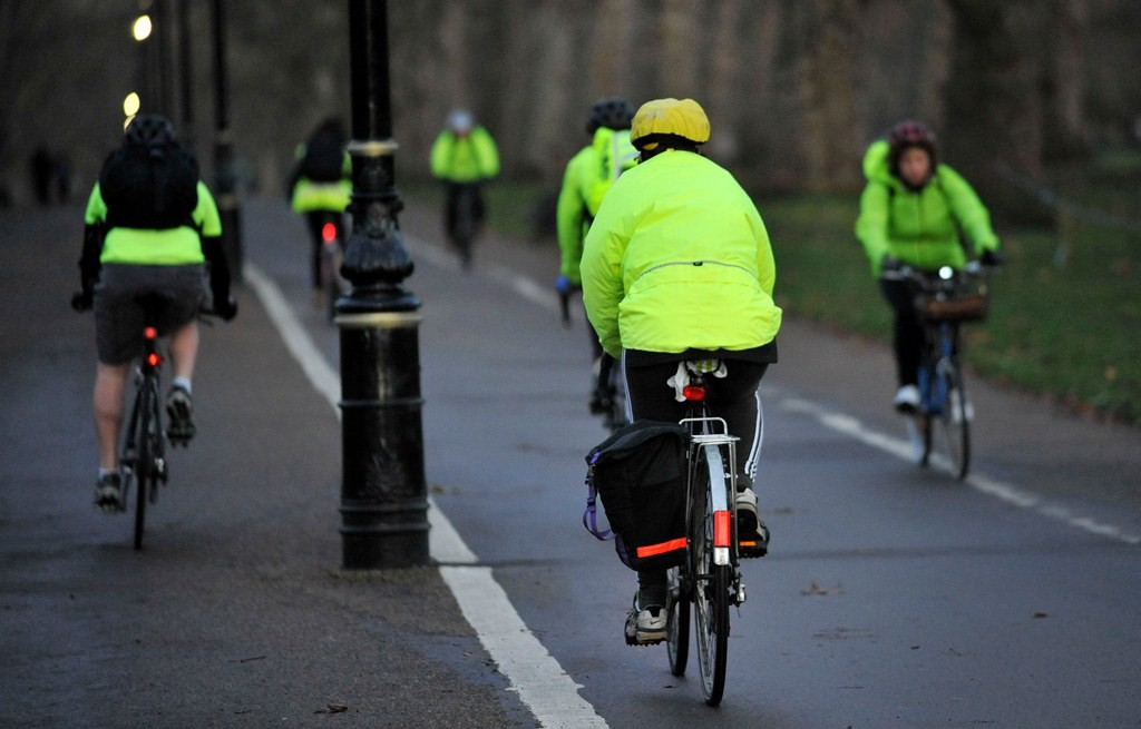 Commuters make their way on bicycles through Hyde Park