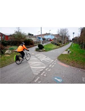 A cyclist crosses a zebra crossing across the Bristol & Bath railway path
