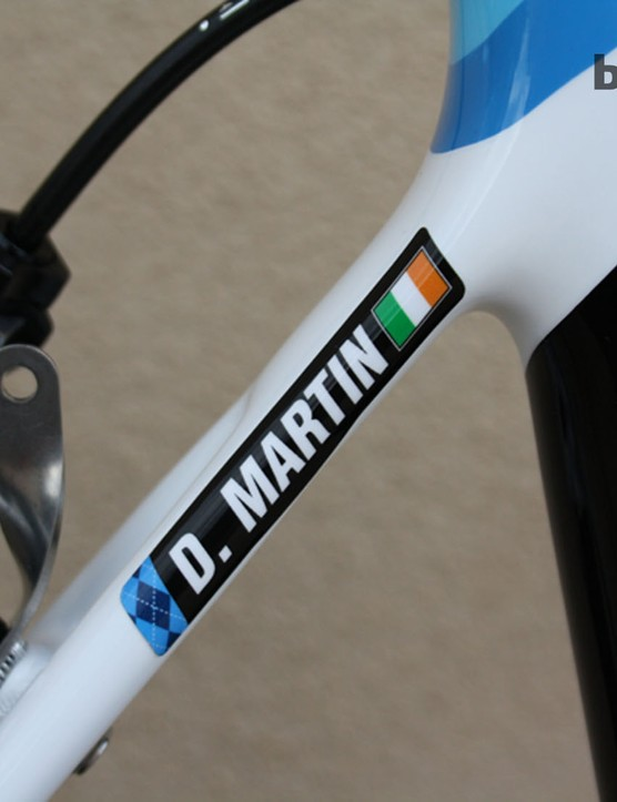 Martin's name was committed to the frame before it left the paint shop; that's not a sticker