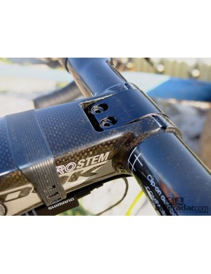 With the magnetic cover removed, you can see the two 3mm bolts holding the handlebar via the thin steel clamp