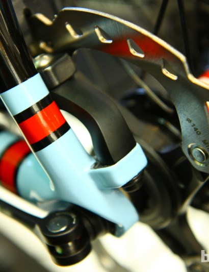 This is what a Reach Around looks like. To position the caliper further back towards the center of the disc, Cannondale created the black arched piece that sits in the light blue protrusion