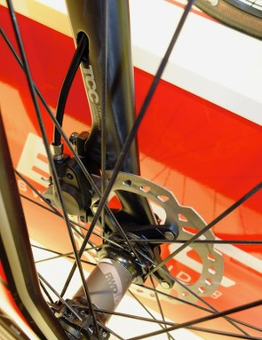 After passing through the headset top cap and steerer tube, the brake hose exits the left fork leg above the calliper