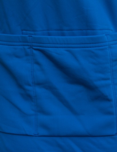 The rear features three jersey-style pockets and reflective striping