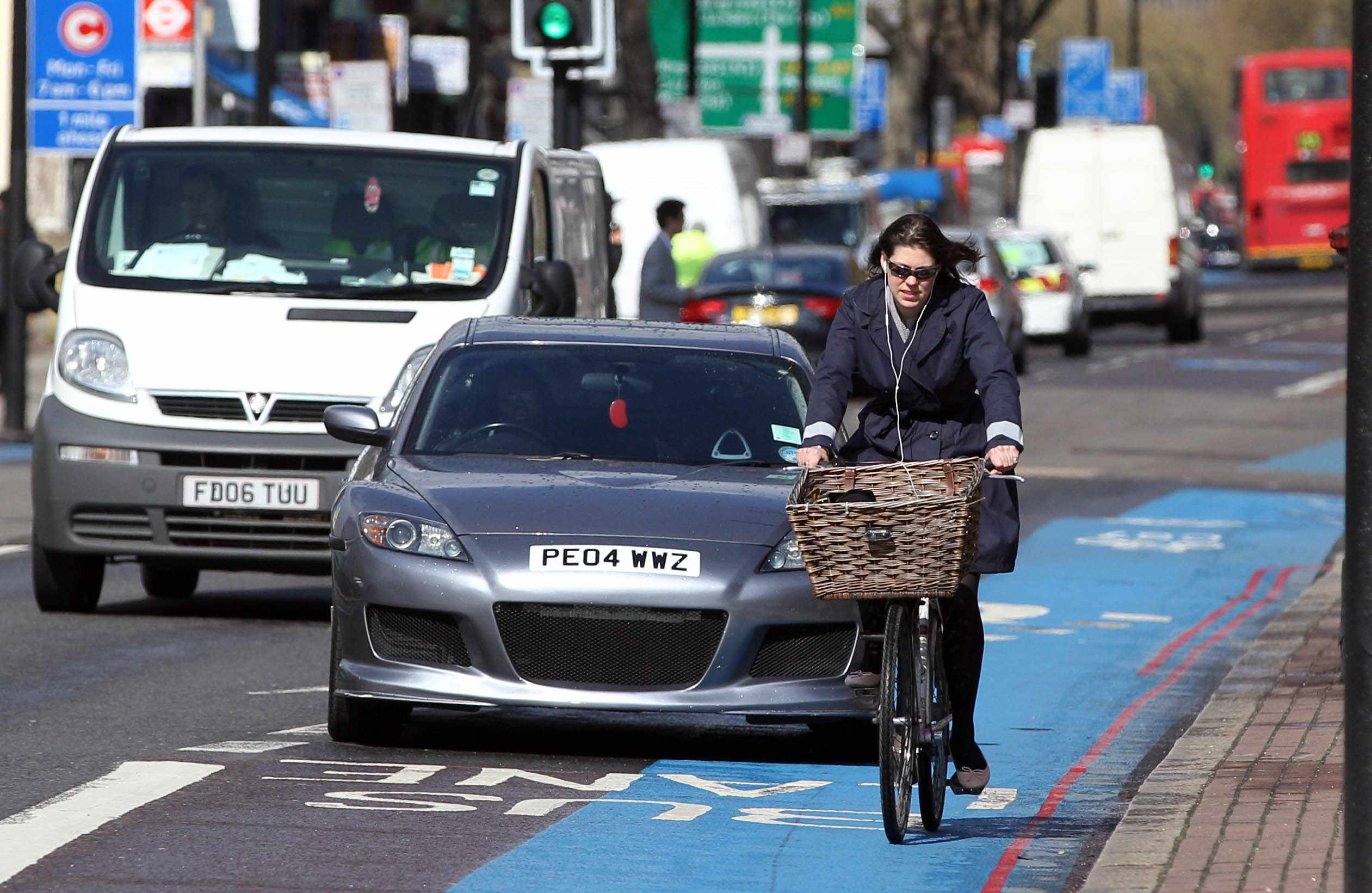 A motorist drives in the bus lane behind a cyclist on an unbordered section of Cycle Superhighway 7