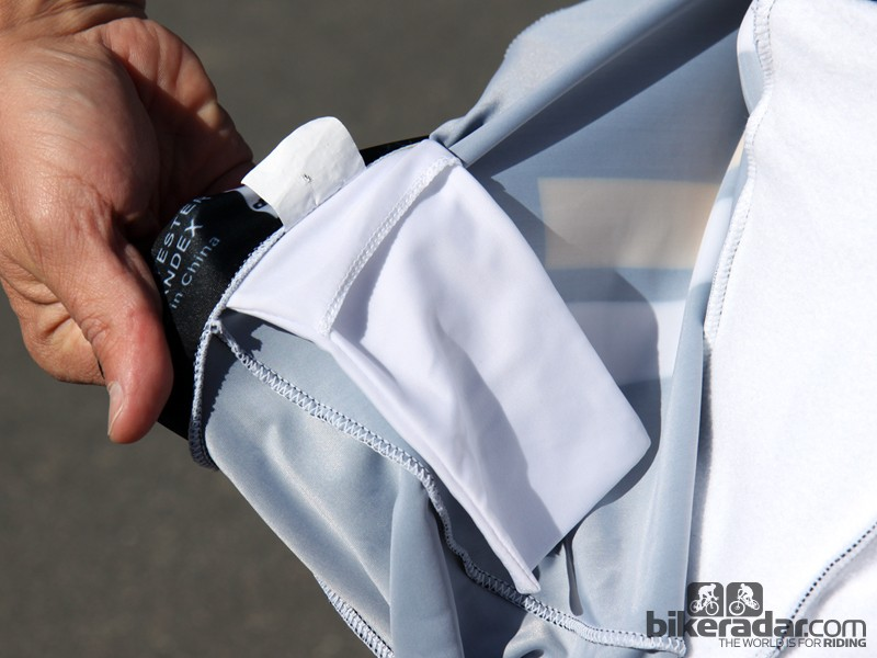 A pocket sits inside the skinsuit at the neck hem. Note the thinner, standard-thickness skinsuit material used on the back on the left with the insulated fabric used on the chest on the right