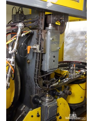 Rim eyelets are installed on this machine. Note the string of eyelets being fed in from up top