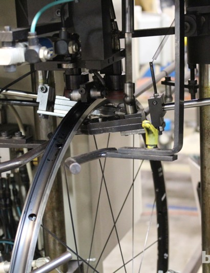 Bontrager has two Holland Mechanics wheel-building machines. This is an older machine that tensions the spokes at the outside of the nipple