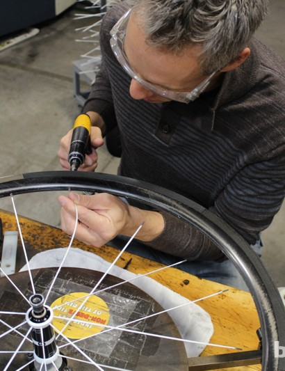 Spokes are attached by connecting two, then skipping two holes, then adding two more, to gradually and evenly add tension to the system