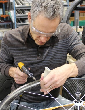 As with the machine nipple attachment, a plastic tool is used to hold the bladed spokes steady while nipples are tightened on