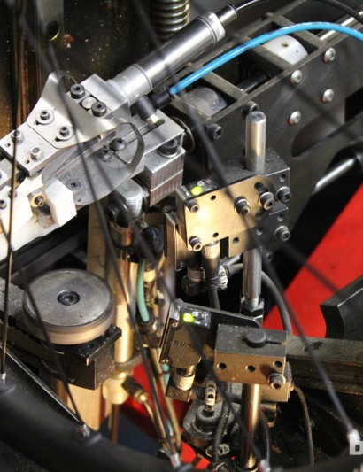 Laser sensors check alignment, signaling in green (shown) and red LED lights. And the machine, curiously, measures trueness of the wheel at the hub, making adjustments at each nipple as it goes