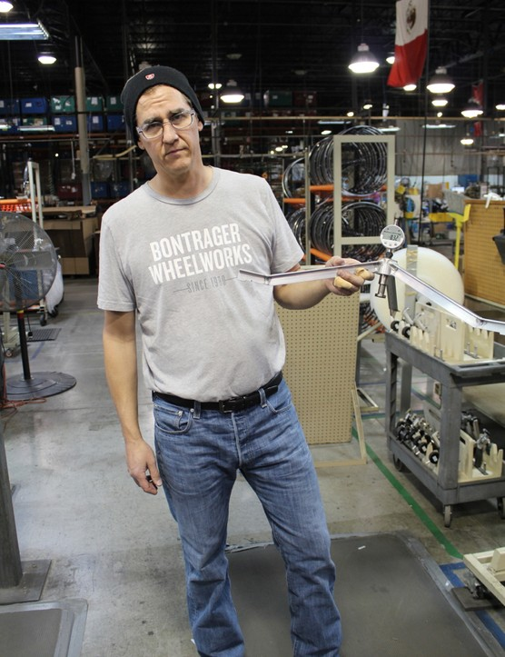 Manufacturing engineer Jeff Bogstad holds his three-legged dish gauge - a custom piece he built 'to settle arguments'