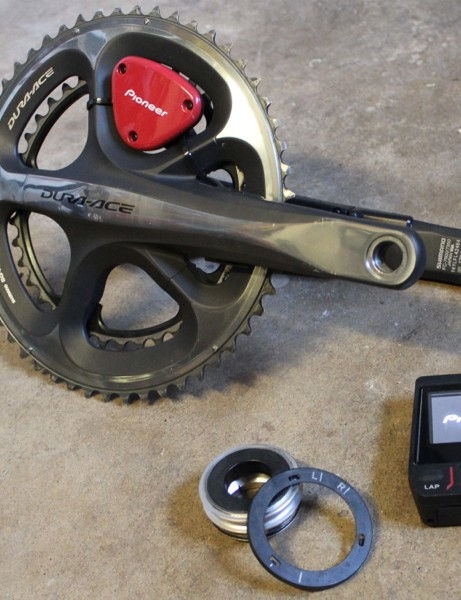 The Pioneer Pedaling Monitor consists of strain gauges on the inside of each crank arm, an ANT+ transmitter (the red piece), magnetic rings that fit on the proprietary bottom bracket and the touchscreen computer