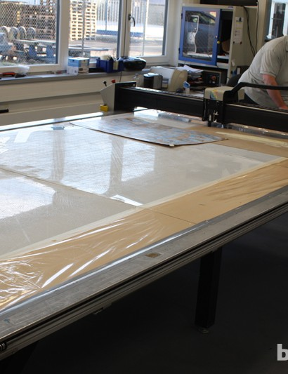 Carbon sheets are loaded onto this CNC cutter, which is capable of cutting intricate shapes for minimum waste
