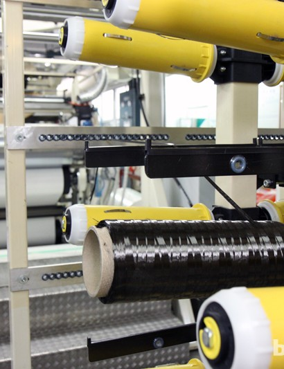Raw carbon fibre is fed off of the spool through a variety of guides and rollers - sort of like a huge sewing machine