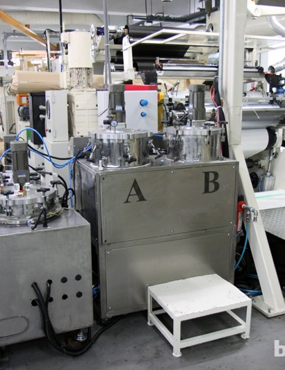 Custom two-part epoxy resins are kept under controlled conditions in these machines before they're mixed together and applied to raw carbon fibre sheets