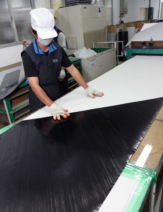 Sections of 45-degree bias ply unidirectional carbon fibre are butted together before new backing paper is applied