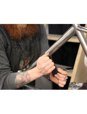 Kevin Batchelor buffs up a freshly finished titanium frame with a strip of Scotch Brite