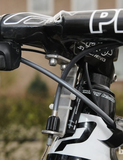 A custom, mechanic-made front cable hanger bolts onto the underside of the stem, and also mounts the Di2 control box. Note the Di2 satellite shifter