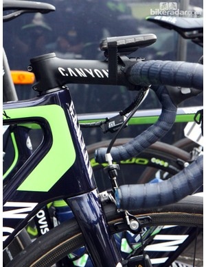 Canyon frames are known for having relatively long head tubes. This Movistar rider opts for a -17° stem to get a lower bar height. Note the strip of tape securing the O.Synce computer, too