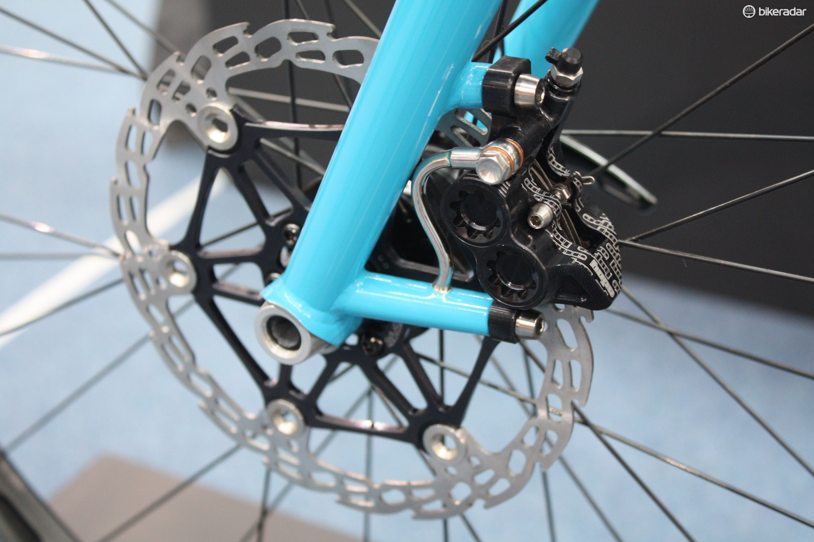 The custom fork neatly integrates the hydraulic lines that lead to the Hope four-pot caliper