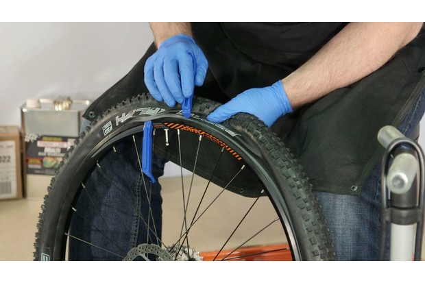 Use a second lever, roughly 5cm away from the first, to begin to pop the bead off the rim