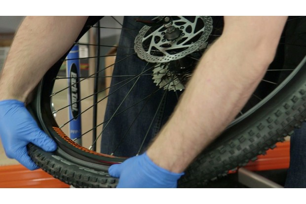 Push the tire bead back onto the rim with your thumbs, taking care not to pinch the tube