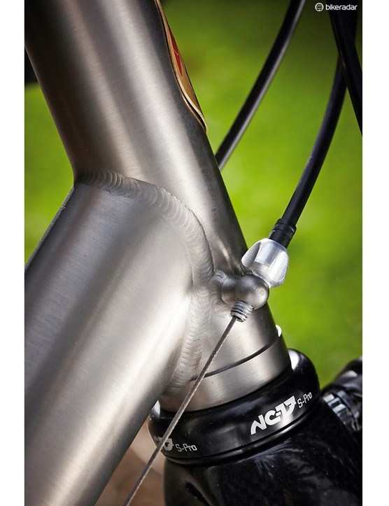 Cable stops on the head tube make structural sense, but create tighter curves in the cables
